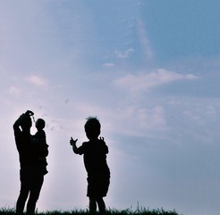 Silhouette of man and two children blowing bubbles