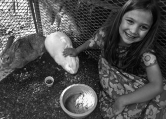 Girl with rabbit and guinea pig, smiling
