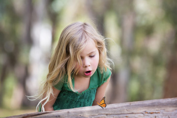 Girl (4-5) looking at butterfly on log