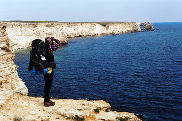 Hiker at cliff edge taking photograph of sea, rear view