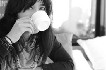 Portrait of woman drinking coffee in room