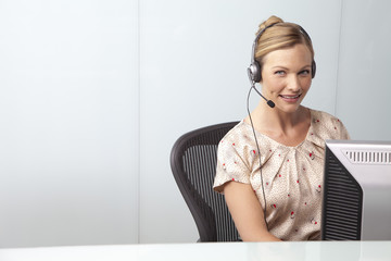 Businesswoman in office wearing telephone headset