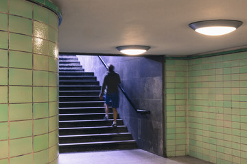 Man walking up staircase from subway