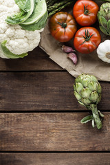 Cauliflower, artichokes, asparagus, garlic and tomatoes on wooden table