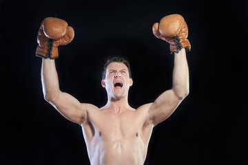 Boxer cheering with hands raised in air