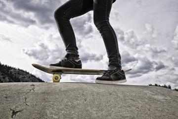 USA, Colorado, Young girl (12-13) standing on skateboard