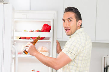 young handsome man looking for food in the fridge