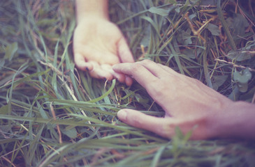 Cropped view of couple's hands on grass, reaching towards each other