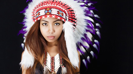 Studio portrait of woman wearing Native American headdress