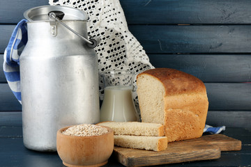 Retro can for milk with fresh bread and glass jug of milk
