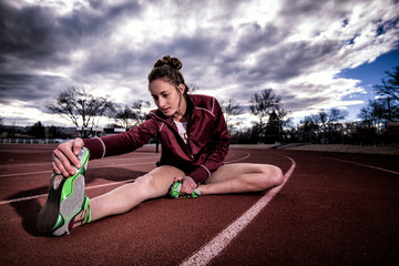 USA, Colorado, Female runner stretching on track