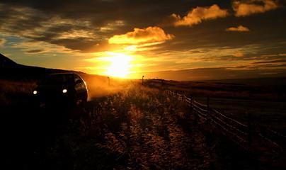 Car in rural landscape at sunset