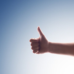 Boy's hand with thumb up against blue background