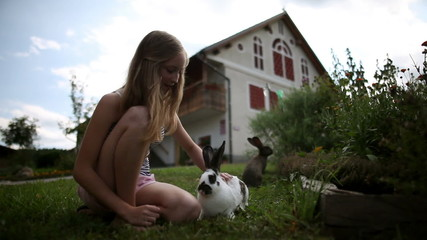 HD1080p: Teenage girl caressing rabbits in front of the house