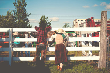 USA, Connecticut, Rear view of couple at rodeo leaning on cattle fence