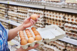 In hands of woman packing eggs in supermarket - 77428784