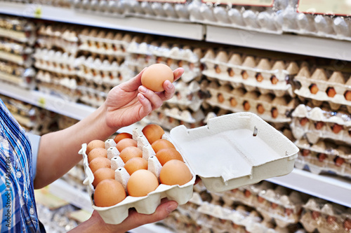 Foto op Canvas Egg In hands of woman packing eggs in supermarket