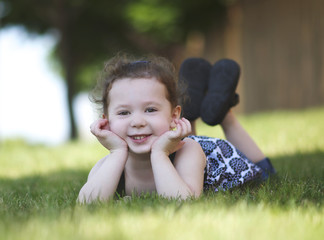 Happy girl (4-5) posing on grass