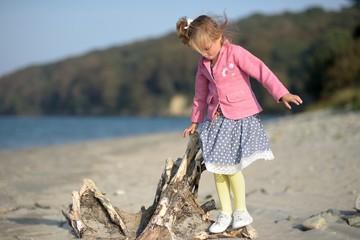 Girl (2-3) standing on log