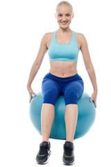 Sporty woman exercising with blue ball