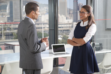 man and woman having discussion outside conference room