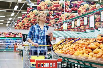Women with cart shopping fruits