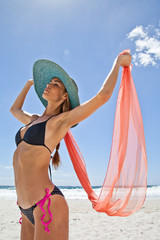 Young woman on beach with a silk scarf