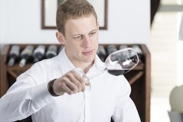 man analyzing a red wine glass.