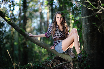Teenage girl sitting on tree in forest