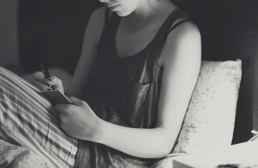 Young woman writing diary in bed