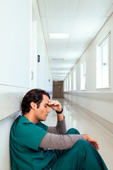 Tired doctor sitting in hospital corridor