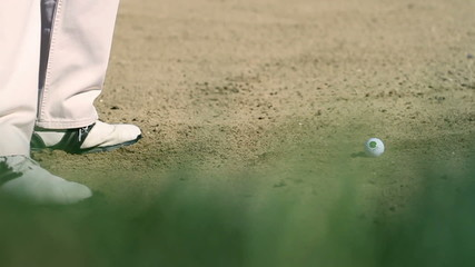 Golfer on a sand course hitting the white golf ball