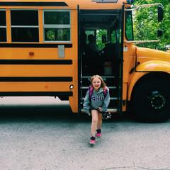 Girl (6-7) getting off school bus