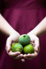 Woman holding 3 fruit