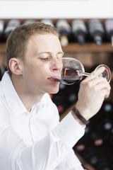man tasting a red wine glass .
