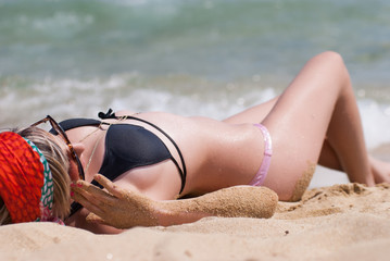 Sexy greek lady lying on sand