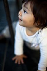 Girl (12-17 months) looking through window