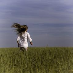 Little girl running in green field