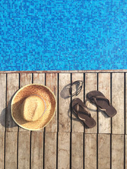 Sun hat, flip-flops and sunglasses by swimming pool