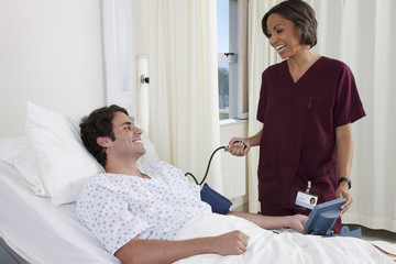 Nurse taking blood pressure of man in hospital