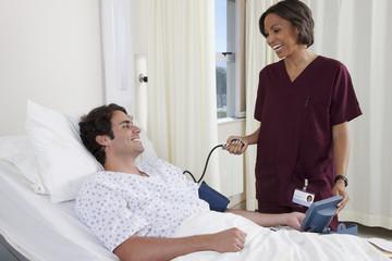 Nurse taking blood pressure of man in hospital