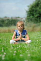 Girl (2-3) sitting on the grass doing yoga
