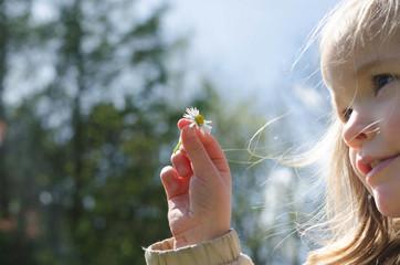 Girl (2-3) holding daisy