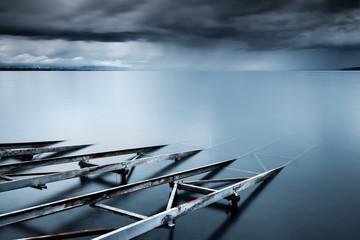Switzerland, Vaud, Villette, Lake Leman, Slipway in still lake with storm clouds on horizon