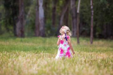 USA, Little girl in field, rear view
