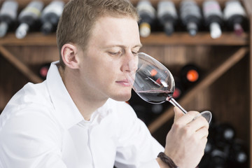 young man smelling a glass of red wine.