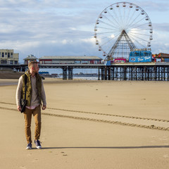 Man at beach and ferris wheel in background