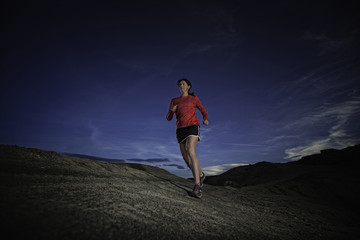 USA, Colorado, Woman cross-country trail running in desert
