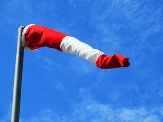 Windbag red white post against sky