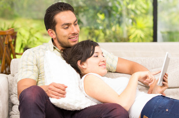 young attractive couple relaxing in the sofa using tablet